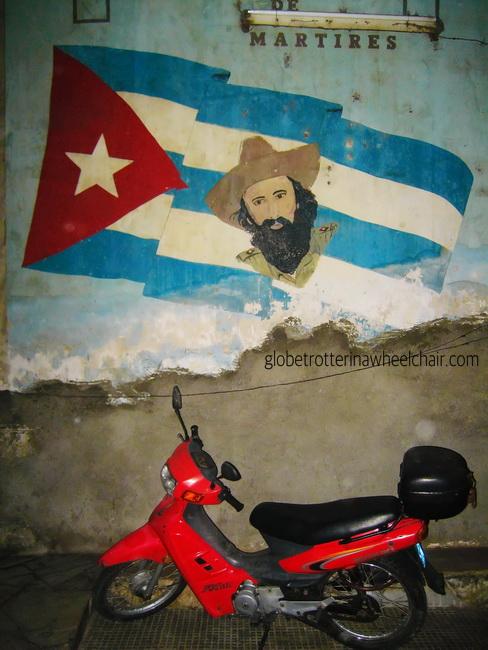 Mural of Cienfuego an Havana flag in a corridor w a motorcycle