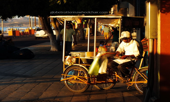 Street vendor at a tricycle in beautiful light from the sunset in La Paz, Mexico
