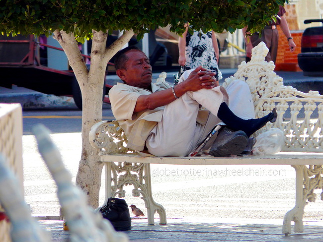 A man with his feet up, relaxing at a bench in La Paz, Mexico