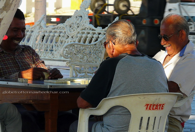 three men playing domino sitting at a table in La Paz, Mexico