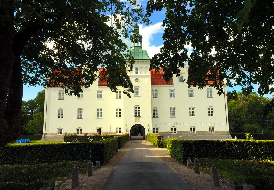 castle in Denmark. White walls, red/ orange roof and greenish spire. - Danish summer