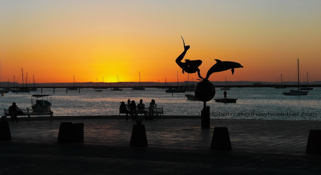 sunset and view of La Paz bay in Mexico, with sculpture of a mermaid and a dolphin in front © curiousKester.com | Kirsten K. Kester