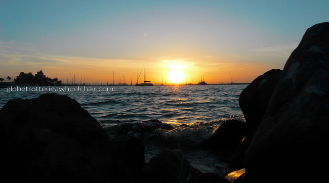 sunset and view of La Paz bay in Mexico, with boats and stones in front © curiousKester.com | Kirsten K. Kester